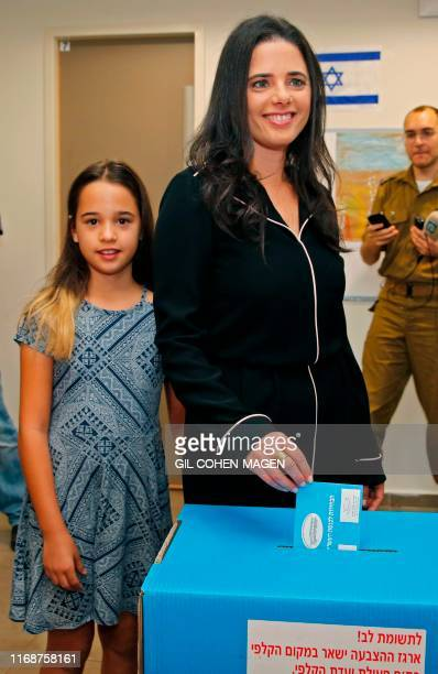 Israel's former justice minister Ayelet Shaked casts her ballot next to her daughter during Israel's parliamentary election at a polling station in...