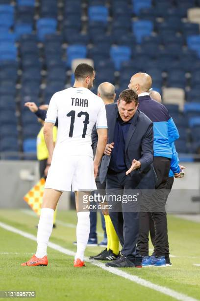 Israel's head coach Andi Herzog speaks with defender Loai Taha during the Euro 2020 Group G football qualification match between Israel and Slovenia...