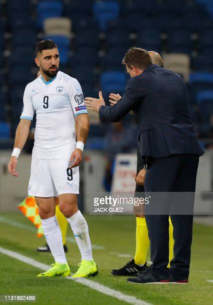 Israel's head coach Andi Herzog speaks with forward Moanes Dabour during the Euro 2020 Group G football qualification match between Israel and...