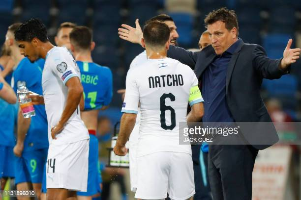 Israel's head coach Andi Herzog speaks with midfielder Bibras Natkho during the Euro 2020 Group G football qualification match between Israel and...