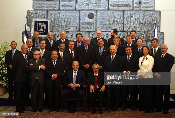 Israel's new Prime Minister Ehud Olmert sits with his 25 member new Cabinet in a group photo in the Presidential residence in Jerusalem Thursday May...