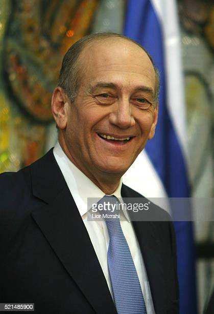 Israel's new Prime Minister Ehud Olmert smiles before a group photo with his 25 member new cabinet in the Presidential residence in Jerusalem...