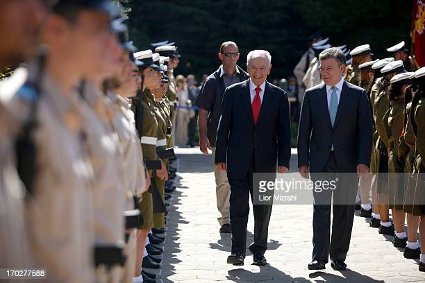 Israel's President Shimon Peres and Colombia's President Juan Manuel Santos pass a guard of honor during a welcoming ceremony at the president's...