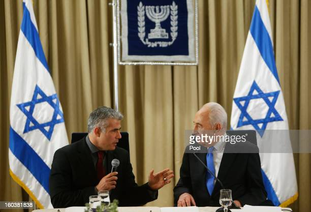 Israel's President Shimon Peres listens as Yair Lapid leader of the Yesh Atid party speaks during their meeting on January 30 2013 in Jerusalem...