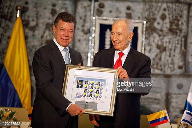 Israel's President Shimon Peres, presents a gift to Colombia's President Juan Manuel Santos after a meeting at the president's residence on June 10,...