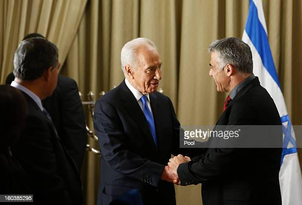 Israel's President Shimon Peres shakes hands with Yair Lapid leader of the Yesh Atid party speaks during their meeting on January 30 2013 in...
