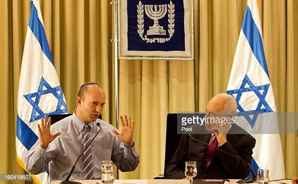 Israel's President Shimon Peres sits with Naftali Bennett head of Israel's Jewish Home party during their meeting at the President's residence on...