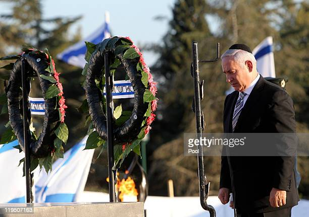 Israel's Prime Minister Benjamin Netanyahu stands in silence next to wreaths during an official memorial ceremony for Theodor Herzl at Mount Herzl...