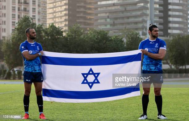 Israel's rugby players pose with a national flag after their first friendly match against the United Arab Emirates' national team in Dubai on March...