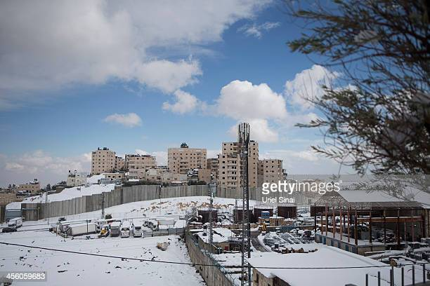 Israel's separation barrier sits covered with snow on December 13 2013 at the West Bank outskits of Jerusalem Heavy storms continued throughout...