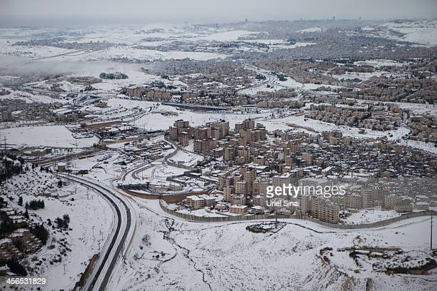 Israel's separation barrier sits covered with snow on December 14 2013 at the West Bank outskits of JerusalemHeavy storms continued throughout Israel...