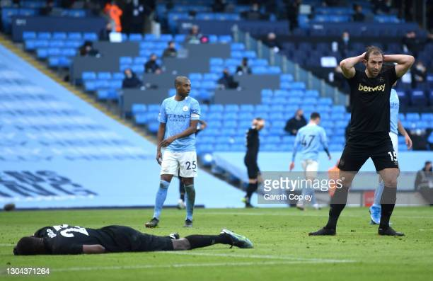 Issa Diop and Craig Dawson of West Ham United react during the Premier League match between Manchester City and West Ham United at Etihad Stadium on...