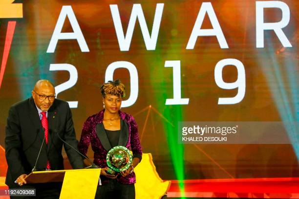 Issa Hayatou President of the Confederation of African Football and Cameroon forward Gaelle Enganamouit receive the award for Womens National Team of...