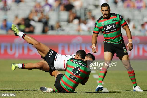 Issac Luke of the Warriors is tackled by Cody Walker of the Rabbitohs during the round one NRL match between the South Sydney Rabbitohs and the New...