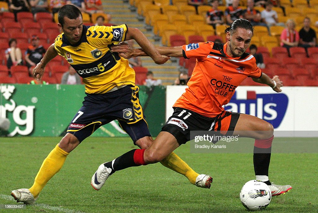 Issey Nakajima-Farran of the Roar is challenged by the defence of John Hutchinson of the Mariners during the round 11 A-League match between the Brisbane Roar and the Central Coast Mariners at Suncorp Stadium on December 17, 2011 in Brisbane, Australia.