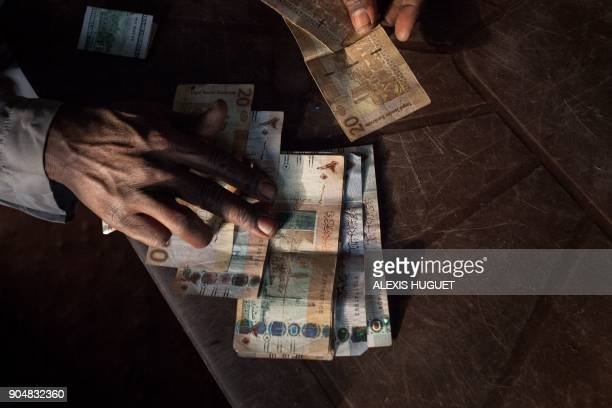 Issouf Zacharia a 47yearsold merchant in Birao northern Central African Republic shows Sudanese bank bills on December 20 2017 Besides the trade...
