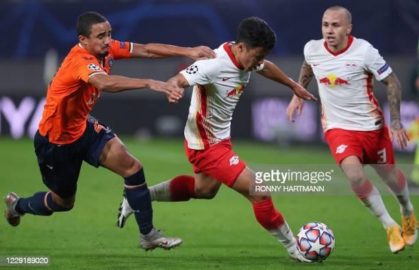 Istanbul Basaksehir's Brazilian defender Rafael and Leipzig's Korean forward Hwang Hee-chan vie for the ball next to Leipzig's Spanish defender...