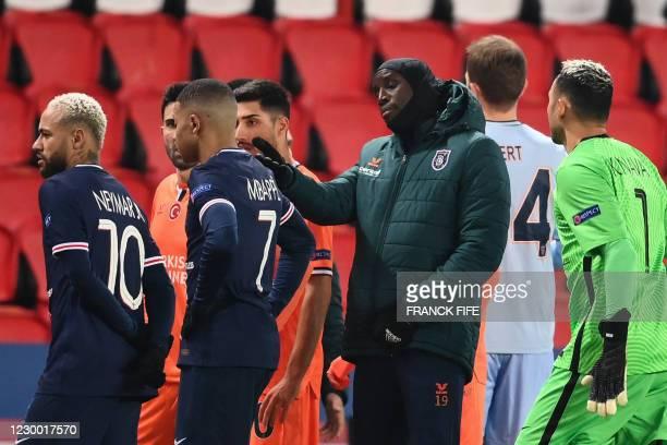 Istanbul Basaksehir's French forward Demba Ba reacts past Paris Saint-Germain's Brazilian forward Neymar and Paris Saint-Germain's French forward...