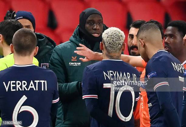 Istanbul Basaksehir's French forward Demba Ba speaks with Paris Saint-Germain's Italian midfielder Marco Verratti, Paris Saint-Germain's Brazilian...