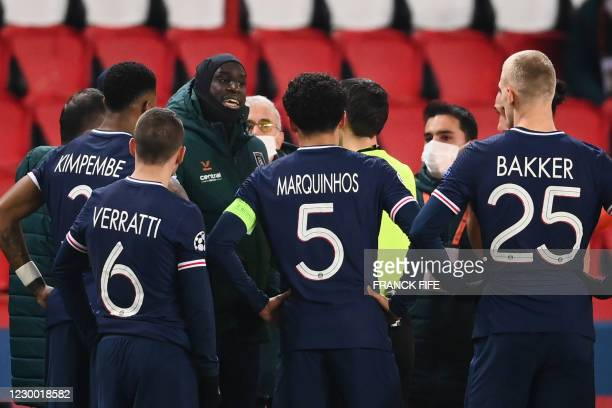 Istanbul Basaksehir's French forward Demba Ba talks to referee after the game was suspended amid allegations of racism by one of the match officials...