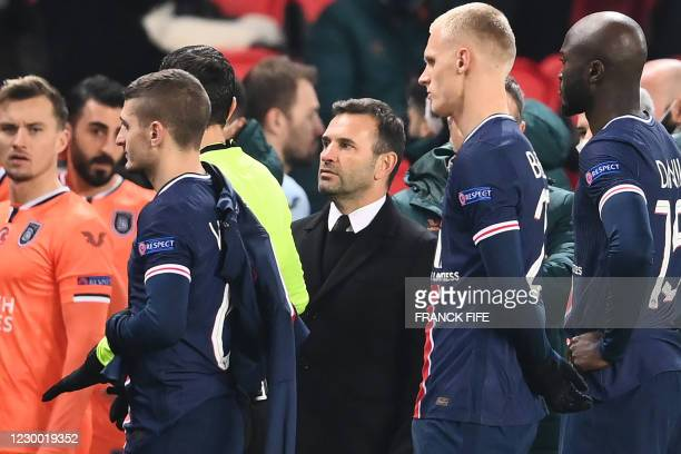 Istanbul Basaksehir's Turkish coach Okan Buruk looks on as he leaves the pitch after the game was suspended amid allegations of racism by one of the...