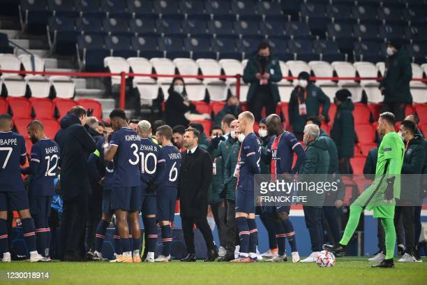 Istanbul Basaksehir's Turkish coach Okan Buruk stands amongst players and staff after the game was suspended amid allegations of racism by one of the...