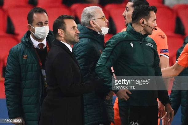 Istanbul Basaksehir's Turkish coach Okan Buruk talks past Romanian 4th referee Sebastian Coltescu after the game was suspended in the first half as...