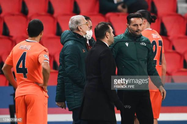 Istanbul Basaksehir's Turkish coach Okan Buruk talks to Romanian 4th referee Sebastian Coltescu after the game was suspended in the first half as the...