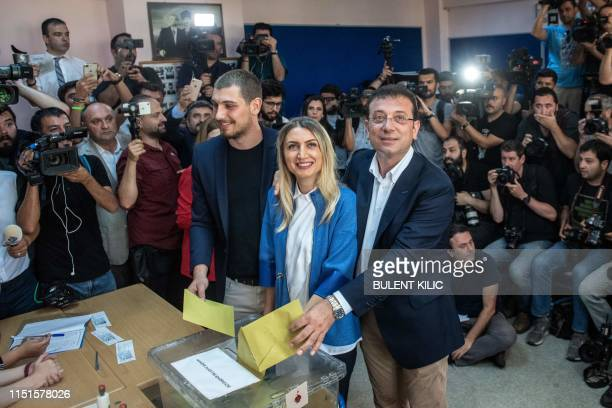 TOPSHOT Istanbul mayoral candidate of the main opposition Republican People's Party Ekrem Imamoglu casts his vote with his wife Dilek Imamoglu and...