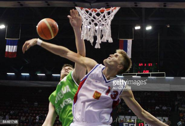Andrey Kirilenko of Russia tries to stop Uros Slokar of Slovenia as he goes for a basket during their third and fourth rank qualifying match for the...