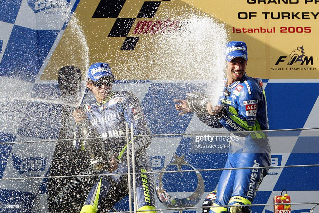 MotoGP champion Italian Marco Melandri (R) celebrates on the podium after winning the Turkish Moto GP ahead of compatriot and world champion Valentino Rossi (L) in Istanbul, 23 October 2005. Melandri, riding a Honda, won the Turkish Moto GP ahead of compatriot and world champion Valentino Rossi who failed in his bid to equal the season's record of legendary Australian Mick Doohan. US Nicky Hayden came third as Melandri, the 2002 champion in the 250 category, took his first GP victory at the inaugural Turkish Moto GP, the 16th and penultimate race of the world championship.