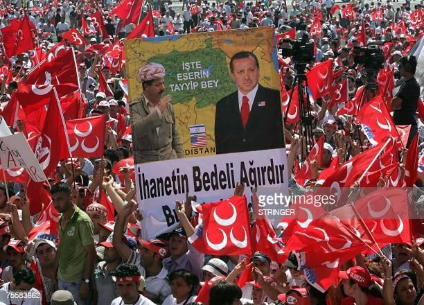 Turks hold a poster featuring Turkish Prime Minister Recep Tayyip Erdogan and Kurdish Democtatic Party leader Massud Barzani reading treason felony's...