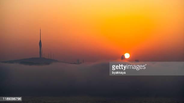 日の出のための雲の中のイスタンブールのテレビラジオ塔 - アナトリア ストックフォトと画像