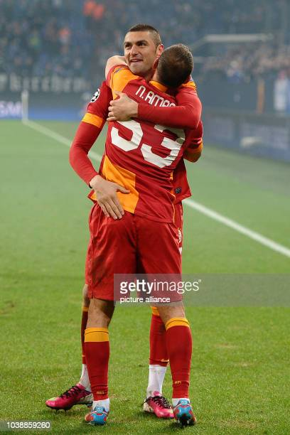 Istanbul's Burak Yilmaz and Nordin Amrabat hug during the UEFA Champions League round of last 16 second leg soccer match between FC Schalke 04 and...