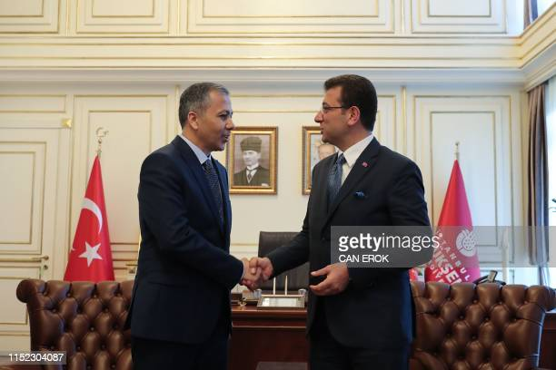 Istanbul's new mayor Ekrem Imamoglu shakes hands with Istanbul's Governor and acting Mayor Ali Yerlikaya during a handover ceremony at the Town Hall...