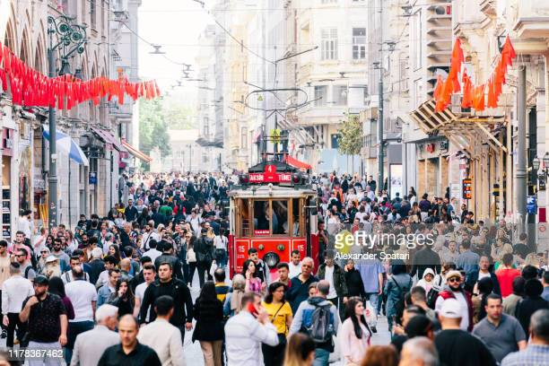istiklal avenue with old red tram and crowds of people, istanbul, turkey - istanbul stockfoto's en -beelden