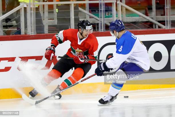 Istvan Sofron of Hungary competes for the puck with Artemi Lakiza of Kazakhstan during the 2018 IIHF Ice Hockey World Championship Division I Group A...
