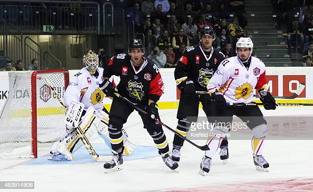István Sofron and Andreas Driendl attending the puck in front of Erik Hanes during the Champions Hockey League group stage game between Krefeld...