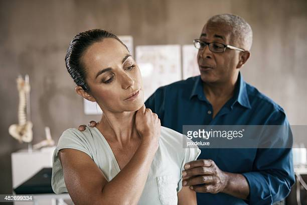 it hurts when i turn it - black massage therapist stock photos and pictures