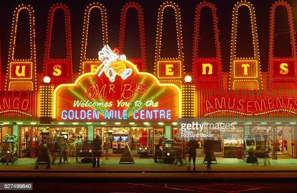 It is nighttime on Blackpool's Golden Mile the seaside resort in Lancashire England Like an English Las Vegas the neon lights glow to entice the...