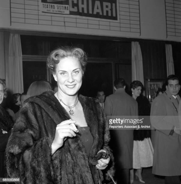 Itaian actress Alida Valli smiling in her fur coat with a cigarette in her fingers at the entrance of the Sistina Theatre staging the Beijing Circus'...