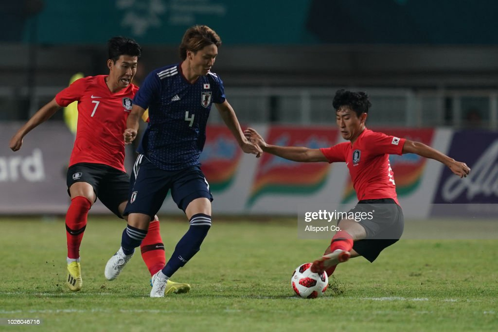 Itakura Kou of Japan challenges Hwang Inbeom of South Korea during the Men's Football gold medal match between South Korea and Japan at the Pakan Sari Stadium on day fourteen of the 18th Asian Games on September 1, 2018 in Jakarta, Indonesia.
