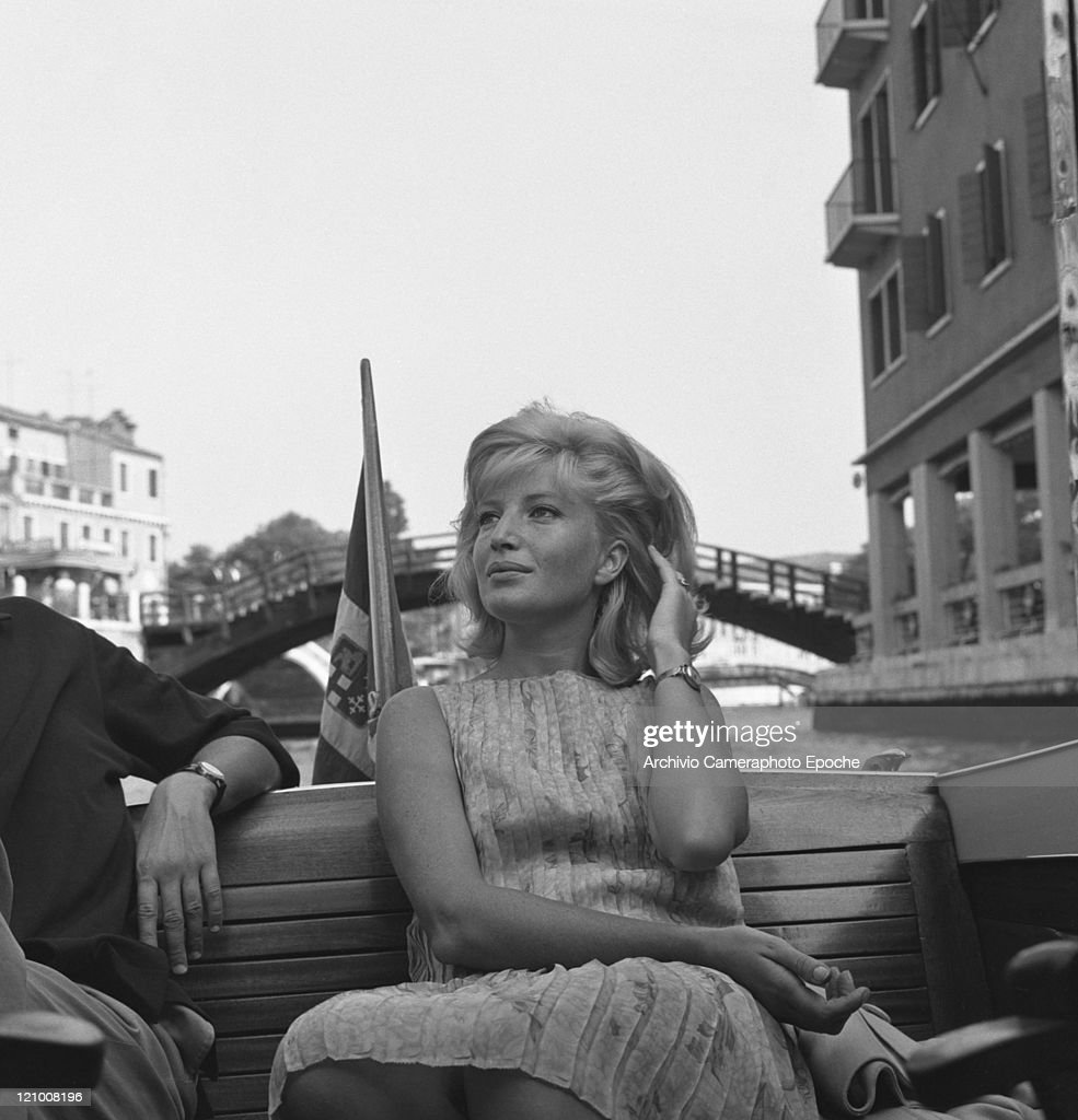 Italian acterss Monica Vitti portrayed while sitting on a water taxi, wearing a pleated floral dress, Canal Grande, Venice 1962.