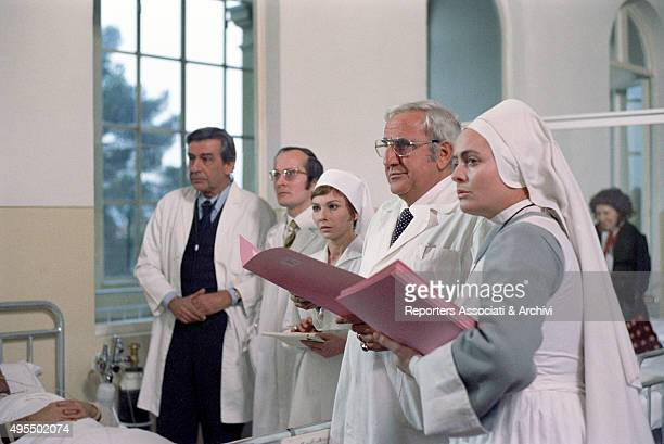 Italian actor Adolfo Celi reading a medical record at the hospital in the film My Friends 1975