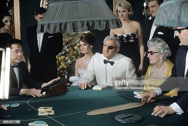 Italian actor Adolfo Celi sitting at a card table in the film Thunderball Beside him French actress Claudine Auger 1965