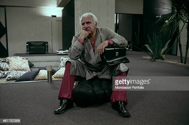 Italian actor Adolfo Celi sitting thoughtful on an armchair in the film Che notte quella notte Italy 1977