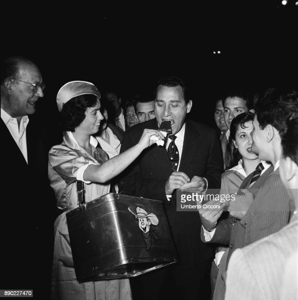 Italian actor Alberto Sordi at the 'Terme di Caracalla' for the opening of the opera season Rome 1956 At the entrance a girl gives him a icecream
