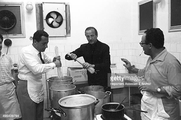 Italian actor Alberto Sordi cooking spaghettis in the kitchen of a restaurant with British actor David Niven and Italian producer Dino De Laurentiis...