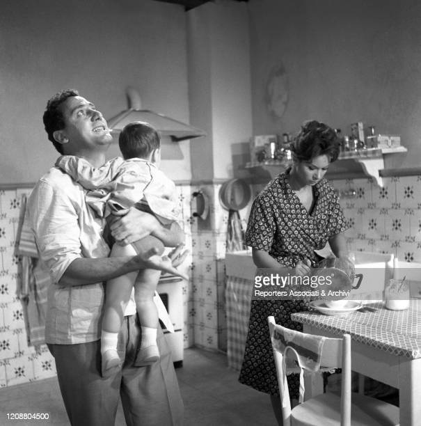 Italian actor Alberto Sordi holding a child. Italian actress Lea Massari pouring the food in a cup in the film A Difficult Life. Italy, 1961