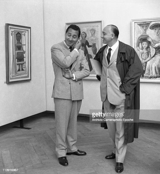 Italian actor Alberto Sordi wearing a doublebrested suit and a tie touching his ear with the artist Guerrini at the Art Biennale in Venice 1958